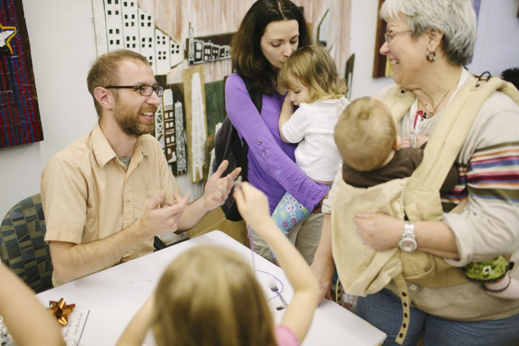 Man happily addresses an intergenerational family