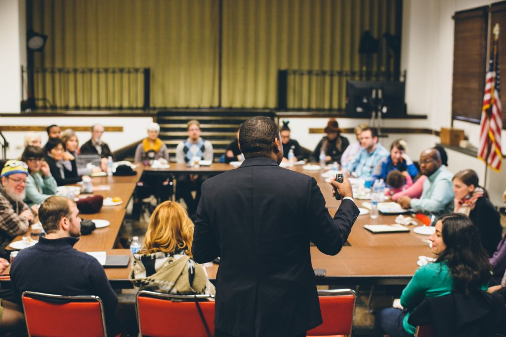 Man in suit addresses community who sit around table