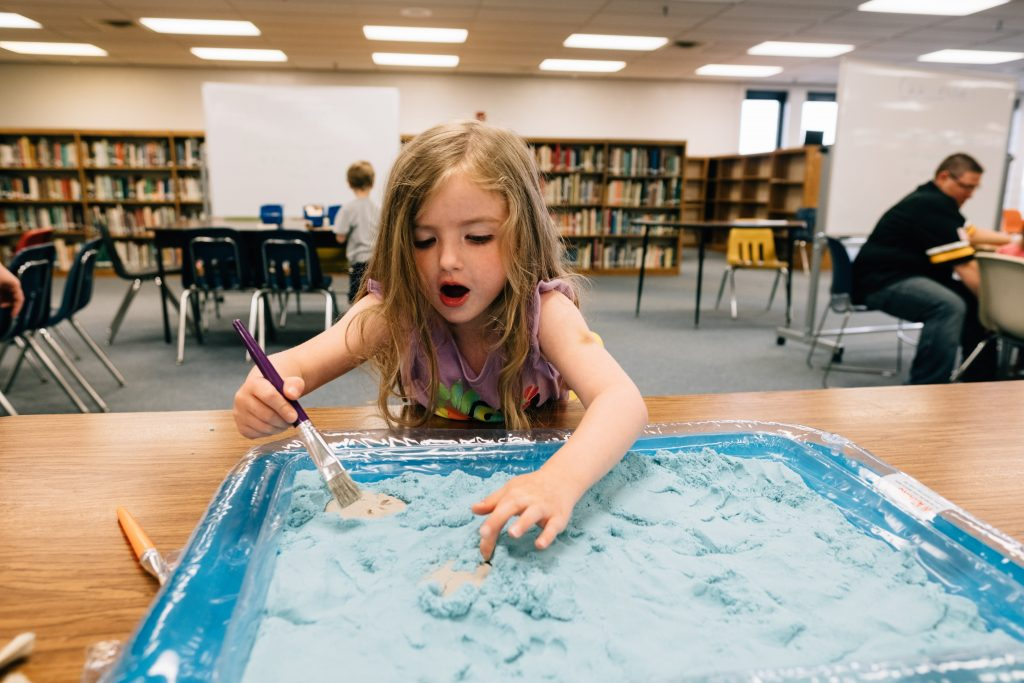 Young girl excitedly playing with blue material in library