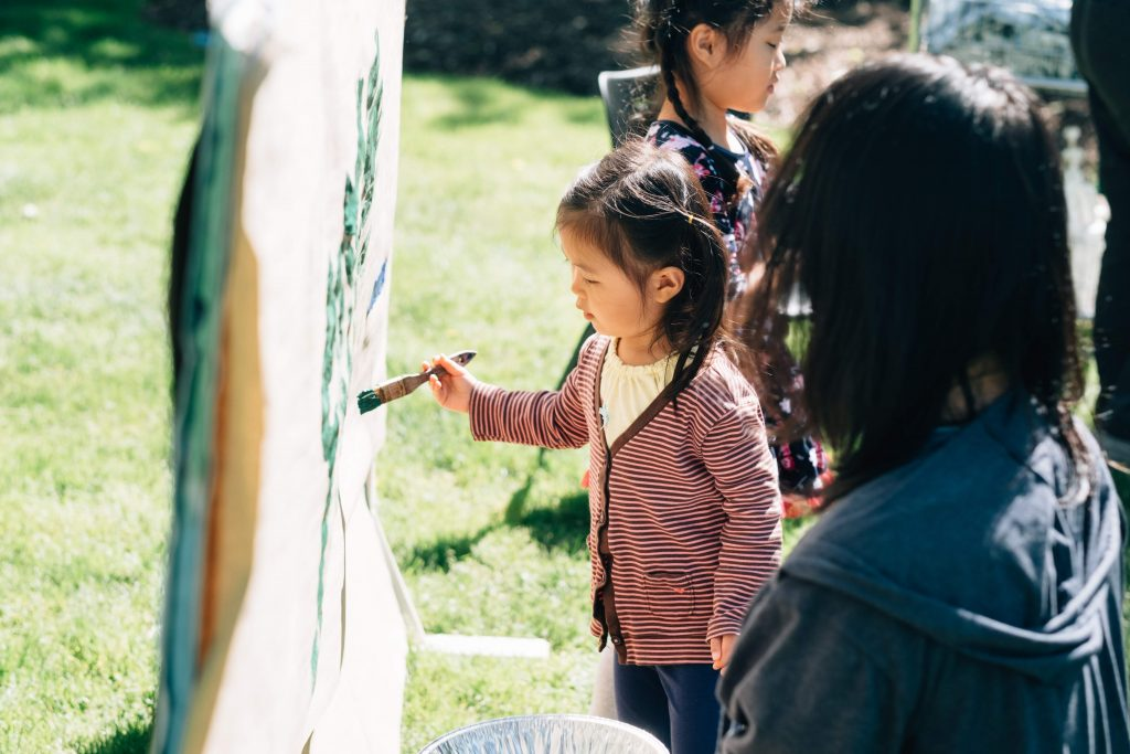 Young girl carefully painting canvas outside
