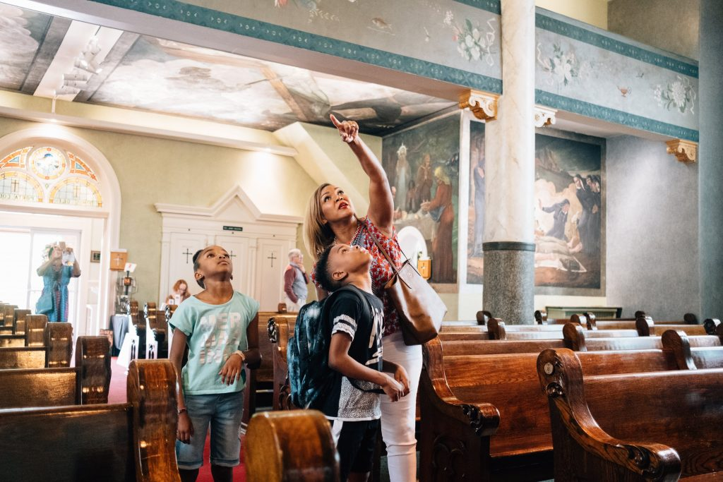 Family looks up in amazement towards ceiling of Millvale church