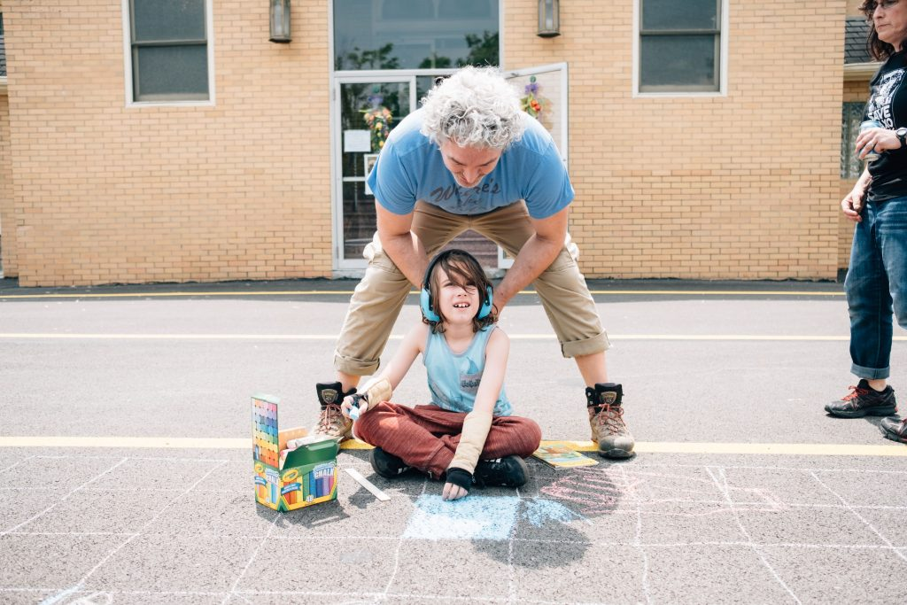 Father embraces son as they pause from chalk drawing to look at camera
