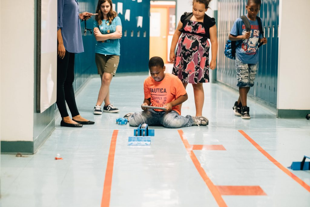 Young boy engineering robot while sitting on floor in public school