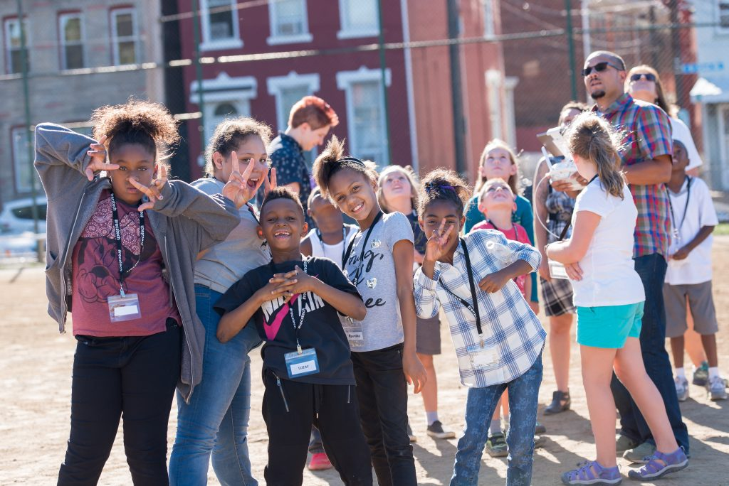 Community of kids excitedly pose together