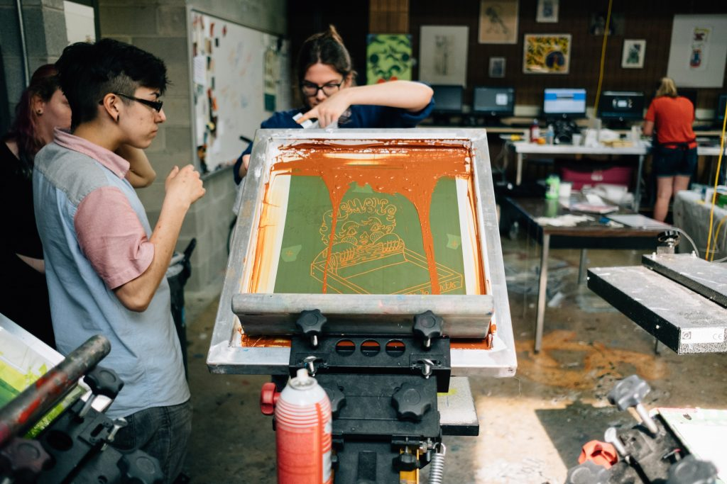 Young adults work with screen printing