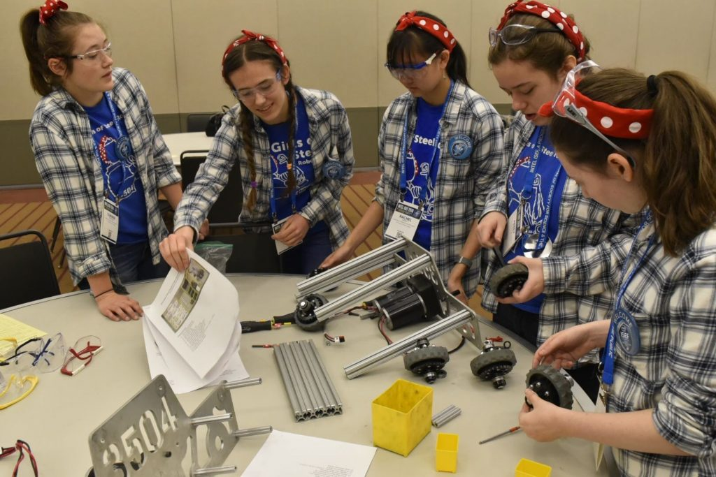 Team of young girls surround table as they explore robotics